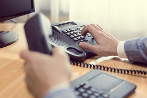 Image for Contact Us Page showing Office Worker Dialing Number on Phone